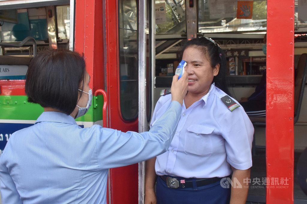 泰國26日凌晨起進入緊急狀態,皇家武裝部隊進入曼谷主要道路設置檢查哨,隨機攔檢車輛。圖為醫護人員幫公車車掌量體溫。中央社記者呂欣憓曼谷攝 109年3月26日
