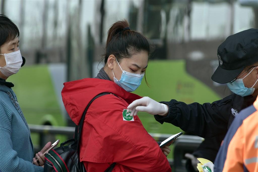 中國國家衛生健康委員會官網通報,武漢肺炎25日新增確診67例,均為境外移入且病例持續攀升,已突破500例。圖為北京八達嶺長城工作人員為遊客發放綠色圓形的「健康碼」。(中新社提供)