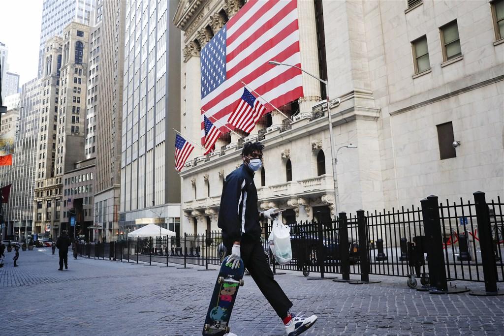 道瓊指數25日勁揚495點,延續24日漲逾11%、寫下87年來最佳紀錄的漲勢。圖為民眾戴口罩經過紐約華爾街。(中新社提供)