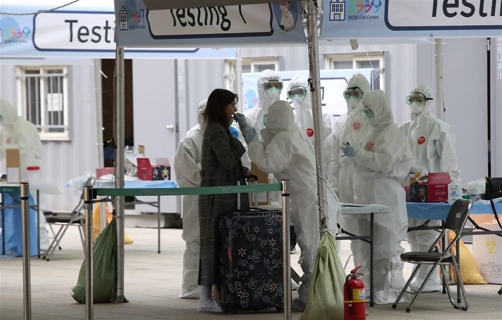 韓國政府宣布,30日起所有飛往韓國的班機,乘客登機前都必須量體溫,超過攝氏37.5度者不得登機。圖為旅客在首爾仁川國際機場外的檢疫站接受採檢。(韓聯社提供)