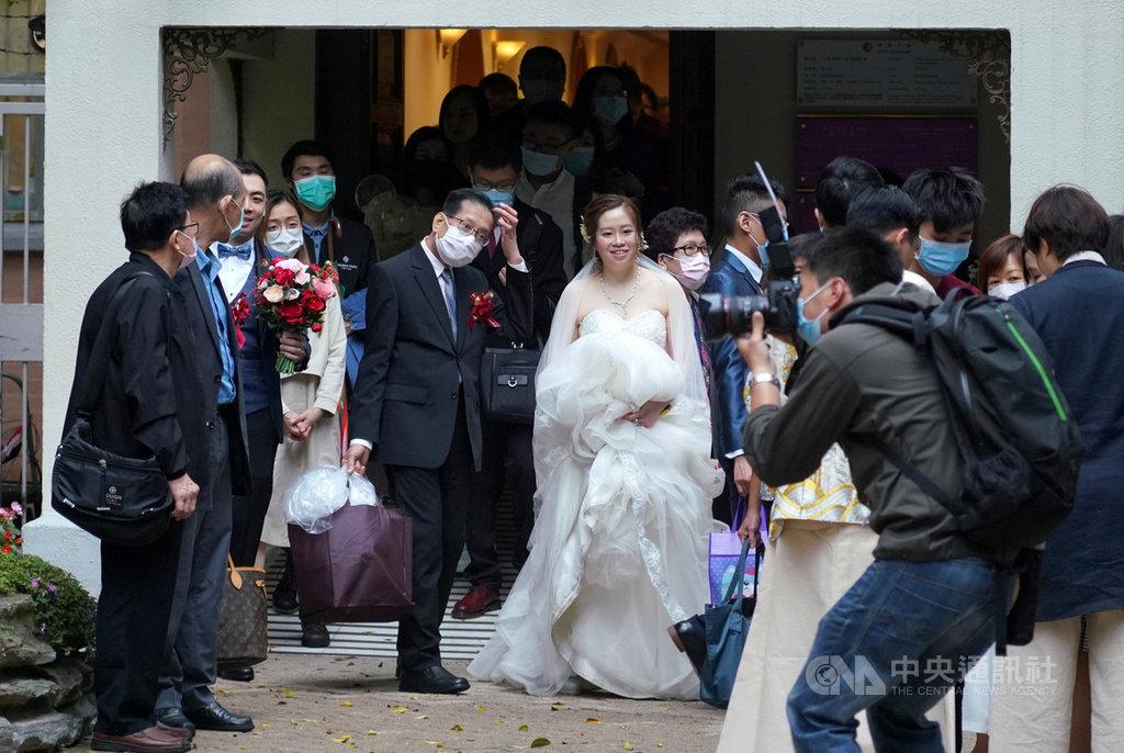 香港當局宣布,29日起禁止4人以上在公共場所聚集,為期14天。其中,舉辦婚禮不得多於20人,且不得供應飲食。圖為3月8日下午,一對新人在香港紅棉路婚姻登記處舉行婚禮,除了新娘,大家都戴上口罩。(中通社提供)中央社 109年3月28日