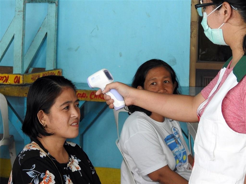 菲律賓今天新增272例武漢肺炎確診病例,增加幅度創新高,確診總數衝上1075例。圖為台灣兒童暨家庭扶助基金會菲律賓分事務所人員14日為社區居民量額溫。(中央社檔案照片)