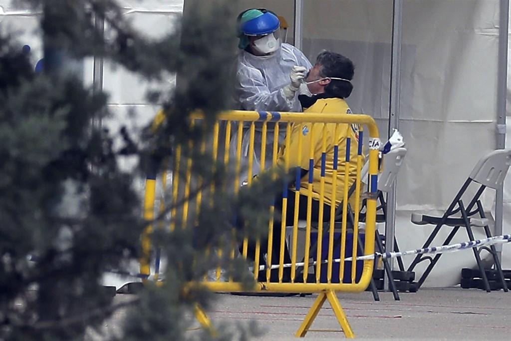 西班牙衛生部30日數據指出,新增6398起武漢肺炎確診病例,累計確診數8萬5195例,超過中國官方通報數字。圖為西班牙馬德里醫護人員對民眾採檢。(美聯社)