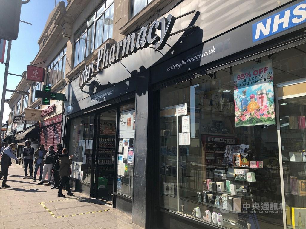 英國下禁足令後,僅有少數店家獲准開業,照片為倫敦的藥局外排起人龍。中央社記者戴雅真倫敦攝 109年3月27日