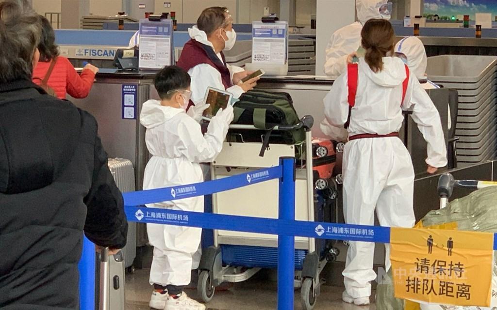 第2班湖北類包機30日晚間起飛,200多名乘客下午已辦理登機。圖為穿著自備防護衣的一家人。中央社記者沈朋達上海攝 109年3月30日
