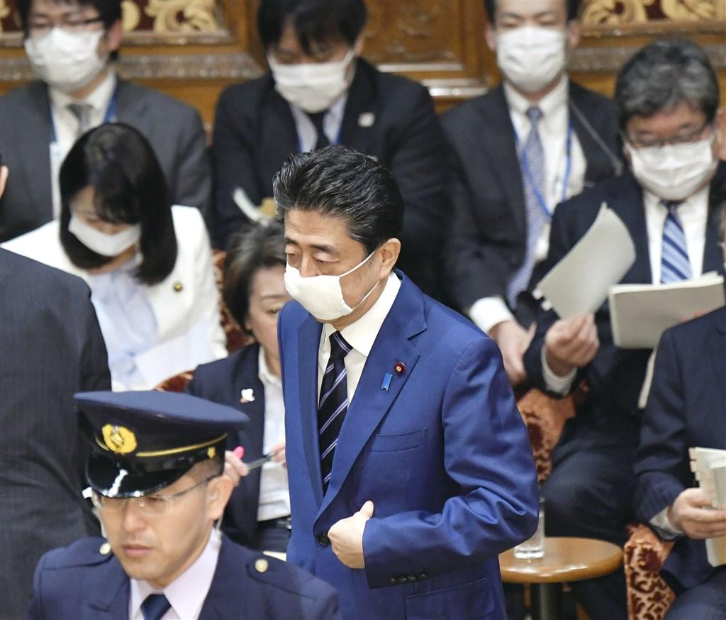日本首相安倍晉三1日在國會備詢時戴上口罩,座位間也用小桌子隔開。(共同社提供)