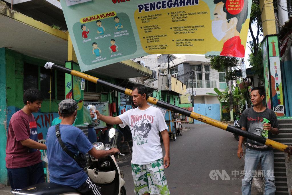 印尼武漢肺炎確診及死亡病例多集中在雅加達,有許多鄰里近來都封起路口,禁止外人近入,保護社區安全,並在路口為居民消毒、量體溫。中央社記者石秀娟雅加達攝  109年4月2日