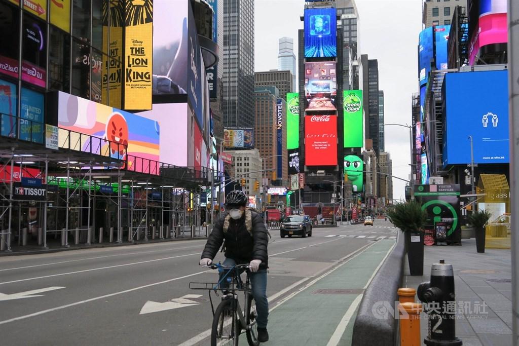 武漢肺炎重創美國,「紐約時報」報導,數據顯示,自跨年前疫情為世人所知後,共43萬人從中國直飛美國,顯示美方動作太慢。圖為美國紐約時報廣場一片冷清,單車騎士也戴起口罩。中央社記者尹俊傑紐約攝 109年4月1日