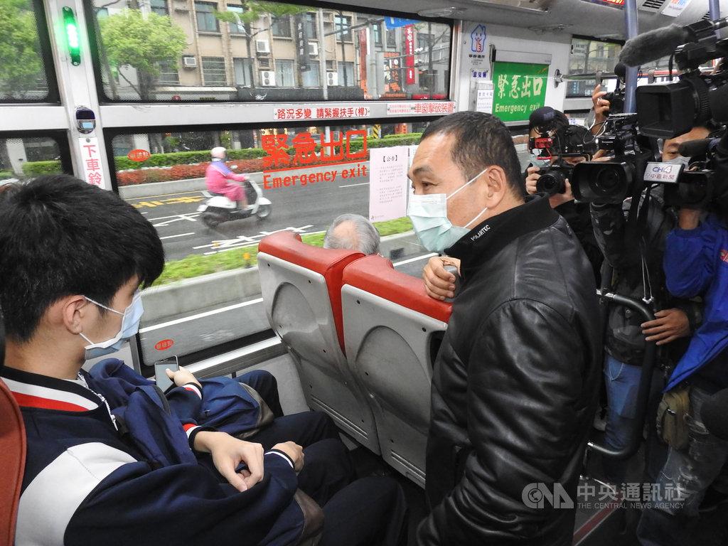 為了提醒乘客注意防疫的重要性,新北市長侯友宜(右)特別到公車站抽查各班公車乘客戴口罩情形,甚至還上公車當面叮嚀乘客。中央社記者王鴻國攝 109年4月6日
