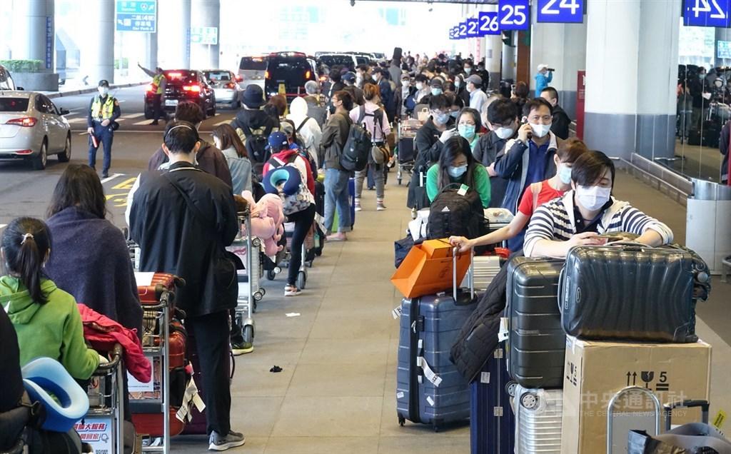 指揮中心宣布,3月30日搭乘華航CI011班機回台的旅客,已有10人確診武漢肺炎。圖為桃機返台旅客排隊搭乘防疫專車。(中央社檔案照片)