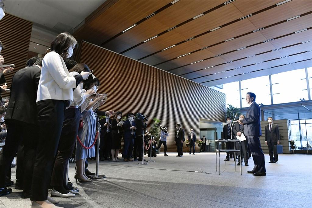 日本首相安倍晉三(右)7日將發布「緊急事態宣言」,預計8日生效。圖為6日記者會現場安倍與記者團採取保持距離措施。(共同社提供)