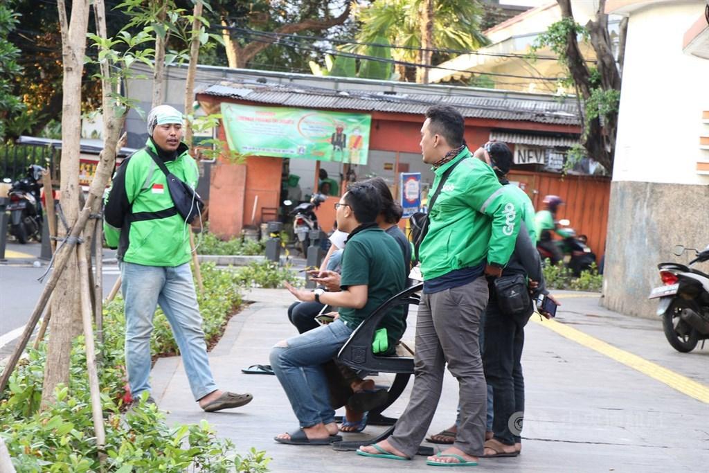 印尼衛生部7日核准雅加達實施大規模社會控制措施,以對抗武漢肺炎。雅加達省政府表示,將禁止線上叫車摩托車騎士接送乘客。圖為雅加達線上叫車騎士4月2日在路邊休息聊天。中央社記者石秀娟雅加達攝 107年4月7日
