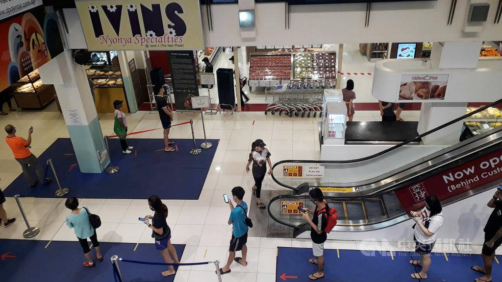 新加坡落實社交安全距離規範,超市購物需依地面安全距離標示排隊。中央社記者黃自強新加坡攝 109年4月8日