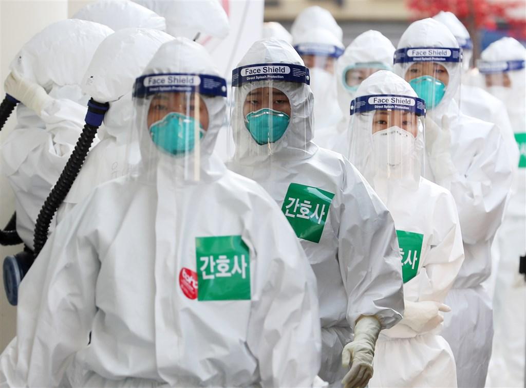 研究人員7日表示,有兩名感染武漢肺炎的韓國年長患者,接受康復者血漿注射治療後皆已康復。圖為韓國大邱7日穿著全身防護裝的醫護人員列隊進入病房。(韓聯社提供)
