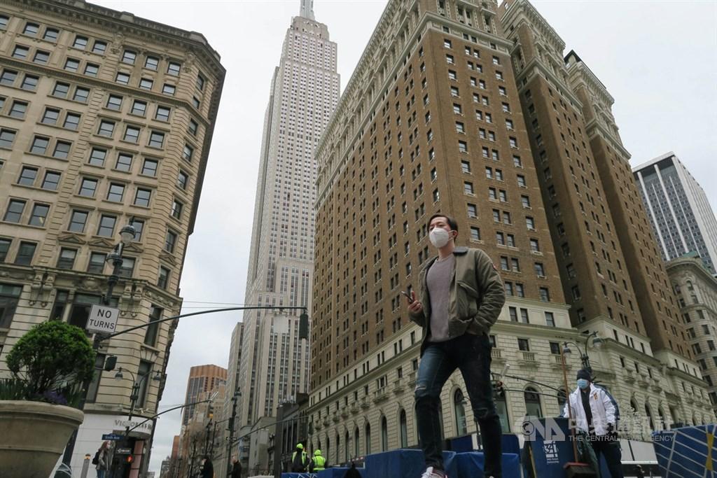 紐約州武漢肺炎疫情持續惡化,大量民眾居家防疫,曼哈頓街頭一片冷清,行經帝國大廈附近先驅廣場的民眾戴口罩防疫。中央社記者尹俊傑紐約攝 109年4月1日