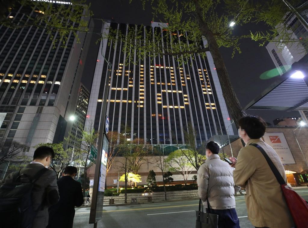 韓國疾病管理本部表示,韓國10日通報新增27起武漢肺炎確診病例,為自2月20日以來首度降至30例以下,境內感染病例累計1萬450例。圖為首爾樂天飯店於9日晚間以客房燈光拼寫「希望」一詞。(韓聯社提供)