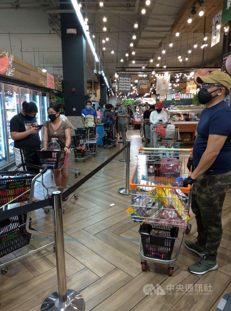大馬尼拉封城後,不少超市結帳區都排著長長的人龍,民眾到超市購物至少要花上1、2個小時才能回家。圖為民眾3日購物排長龍。中央社記者陳妍君馬尼拉攝 109年4月14日