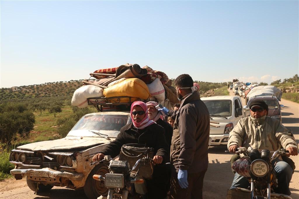 土耳其與俄羅斯同意在敘利亞伊德利布省停火後,大批難民從土耳其攜家帶眷返鄉,然而他們還必須面對武漢肺炎病毒。圖為邊界人員為返鄉者測量體溫。(安納杜魯新聞社提供)