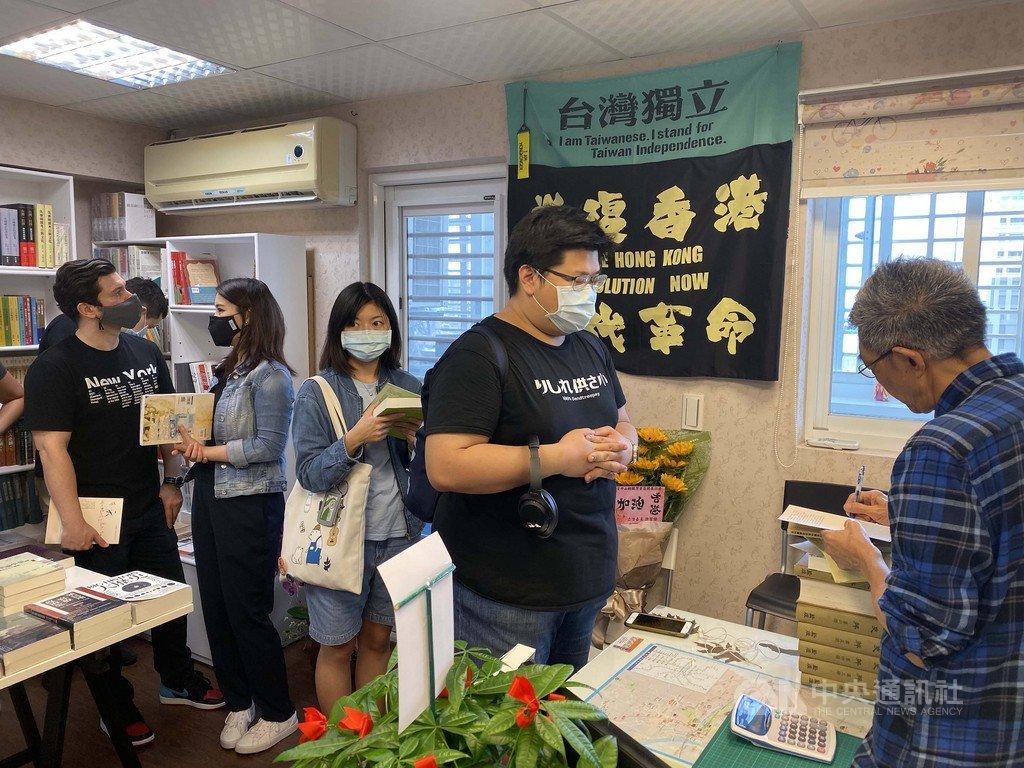 銅鑼灣書店25日在台北開幕,中央社記者28日實地走訪,發現即便是平日時段,仍有不少民眾慕名前來,排隊等待結帳並要求店主林榮基在他們購買的書上簽名。中央社記者賴言曦攝 109年4月28日
