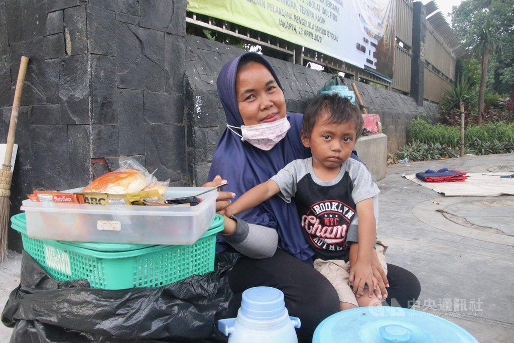 印尼民眾蘇里亞蒂25日帶著孫子賣即溶咖啡,清真寺因疫情關閉,幾乎沒有人潮,也沒有生意,但她說,會用守齋學到的智慧面對困難。中央社記者石秀娟雅加達攝 109年4月28日