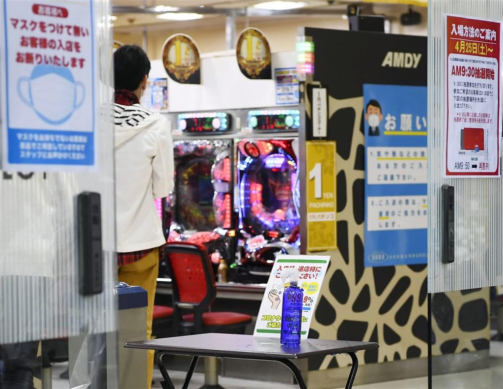 日本緊急事態宣言公布後,各地方首長籲請非必要店家停業,但小鋼珠業者中有人配合、也有人不理會,讓地方首長公布店家名稱。圖為日本東京都部分柏青哥照常營業。(共同社提供)