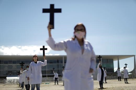 巴西一群護士1日在總統府前安靜示威,手持十字架紀念因武漢肺炎殉職的同事,卻遭到巴西總統波索納洛支持者攻擊。(路透社提供)