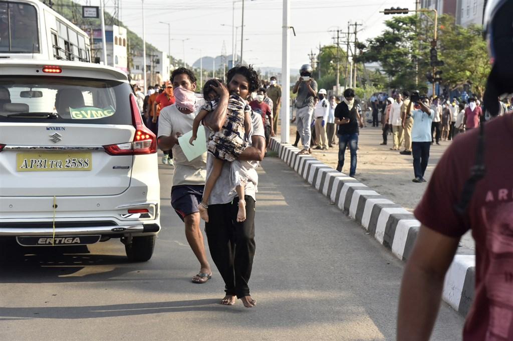 印度7日LG Polymers旗下一間化學工廠瓦斯外洩,造成至少6人罹難、近千人住院。圖為當地民眾抱著小孩逃離瓦斯外洩現場。(美聯社提供)