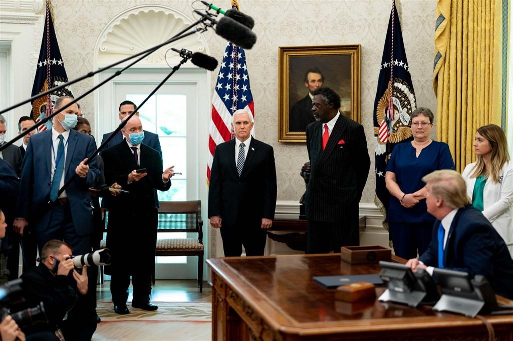 白宮已指示在西廂工作的幕僚群在辦公室必須一直戴著口罩。圖為美國總統川普(右前)6日在白宮西廂的辦公室接受記者訪問,幕僚群大多尚未戴上口罩。(圖取自flickr;作者The White House,版權屬公眾領域)