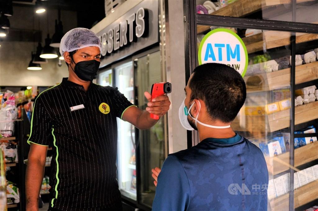 新德里屬於疫情嚴重的紅色區域,民眾進入超商購物需測量體溫及乾洗手。圖為一間連鎖超商店員為顧客量體溫。中央社記者康世人新德里攝 109年5月6日