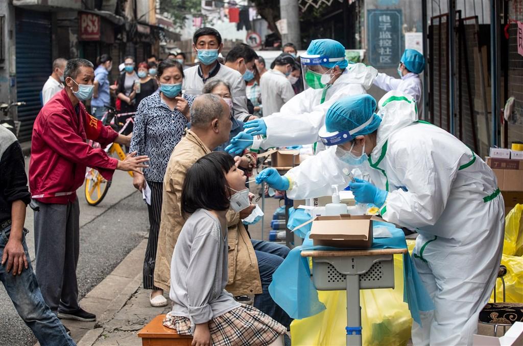 擁有1100萬人口的中國武漢市展開大規模篩檢,戶外篩檢站前大排長龍。(法新社提供)