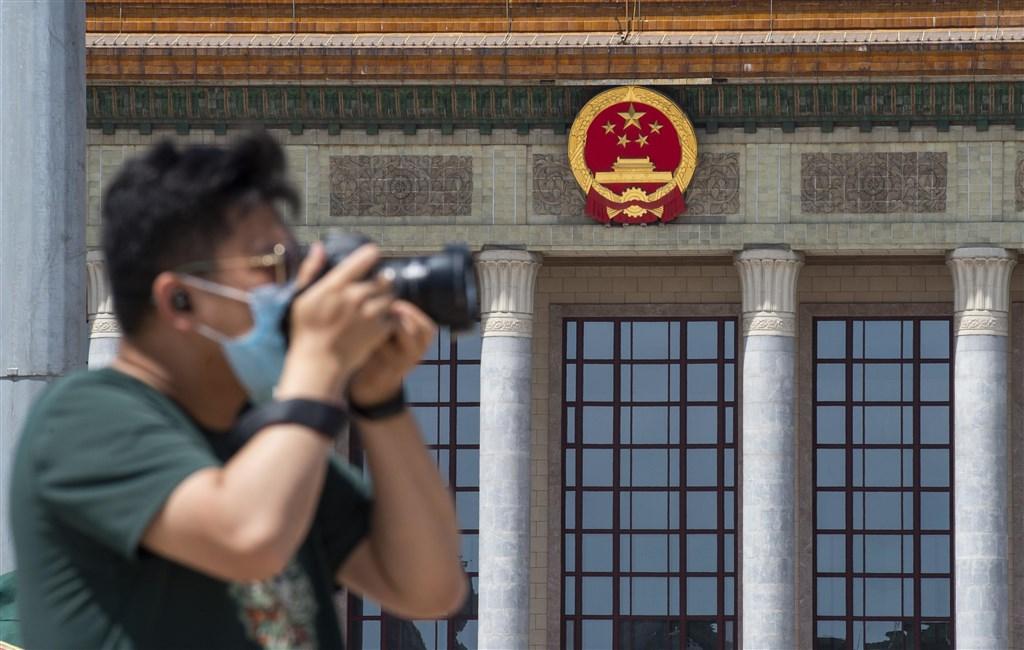 中國13屆全國人大第3次會議22日至28日在北京召開,預計審議備受關注的「香港版國安法」。圖為民眾在人民大會堂前拍照。(中新社提供)
