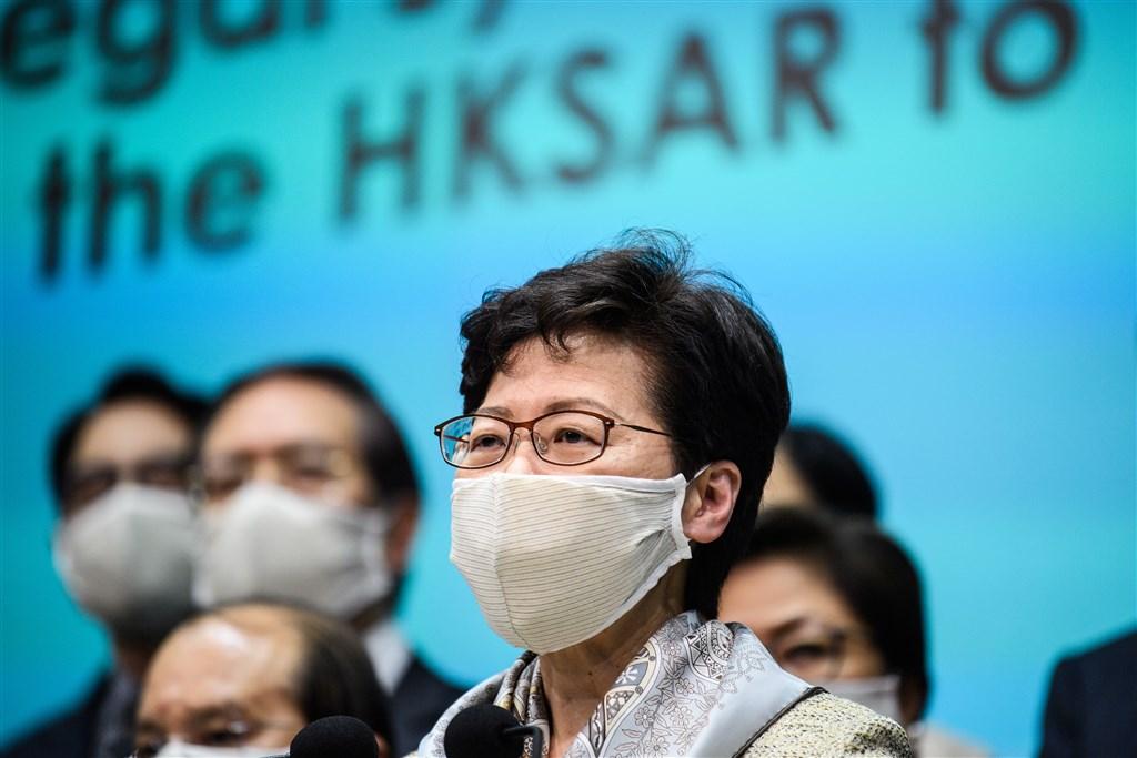 香港行政長官林鄭月娥(前)22日晚間會見媒體時表示,未來的港區維護國家安全法主要由港方機構執法。(法新社提供)