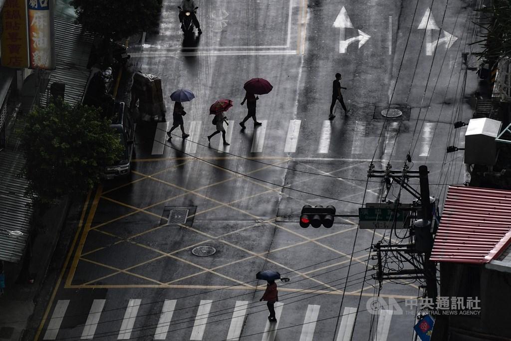 中央氣象局表示,25日各地山區、東半部及大台北地區要注意局部短暫雷陣雨,一波梅雨鋒面26日至28日在台灣滯留,西半部及東北部應防局部大雨。圖為新北街頭民眾撐傘避雨。中央社記者林俊耀攝 109年5月25日