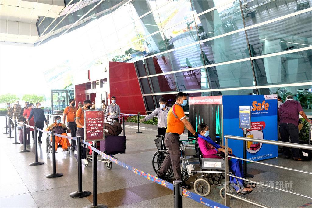 印度航空因武漢肺炎疫情停擺2個多月後,25日國內航線復航,乘客在保持社交距離下排隊等待掃描行李。中央社記者康世人新德里攝  109年5月25日