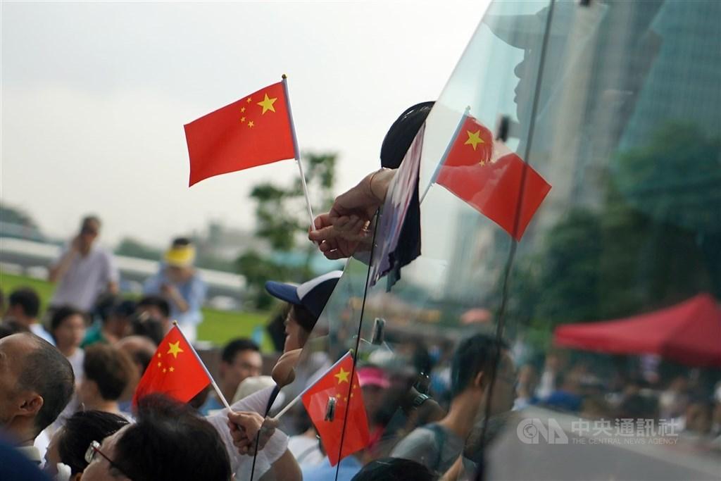 香港立法會27日將對國歌條例草案恢復二讀以便實施中國國歌法。圖為2019年反送中運動期間,建制派立法會議員舉辦集會支持港警,參與民眾手持中國國旗表達立場。(中央社檔案照片)
