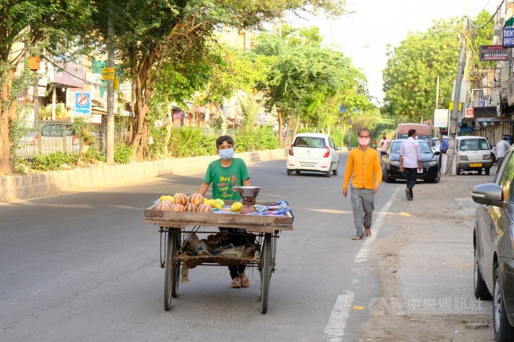 印度病故人數不到一個月翻3倍,過去一週增加1000多人;據約翰霍普金斯大學數據,印度的確診28日來到16萬5069例,將近中國的一倍,也超過伊朗。圖為少年推車沿路兜售水果。中央社記者康世人新德里攝 109年5月6日