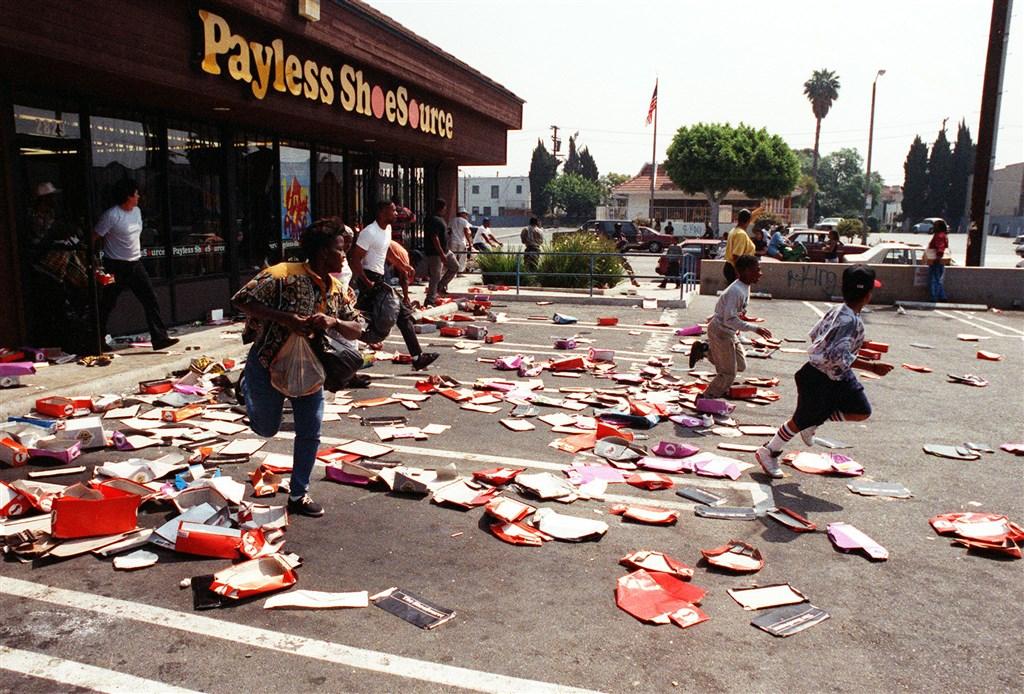 美國武漢肺炎疫情未退又發生警察暴力激化種族對立,令人聯想到1992年洛杉磯暴動的亂世景象。圖為1992年洛杉磯暴動期間搶劫事件頻傳。(檔案照片/美聯社)