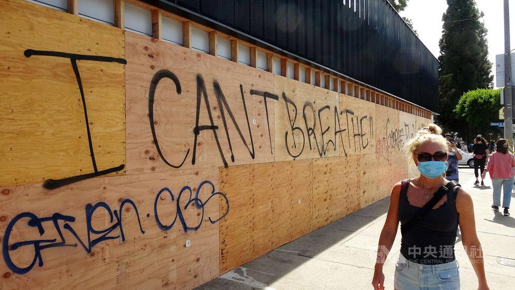 美國反種族歧視的示威活動,衍生趁亂打劫、破壞商家的犯罪行為,圖為商家外圍釘上木板防止砸店,上面被抗議者塗鴉口號「我不能呼吸」。中央社記者林宏翰洛杉磯攝 109年6月1日