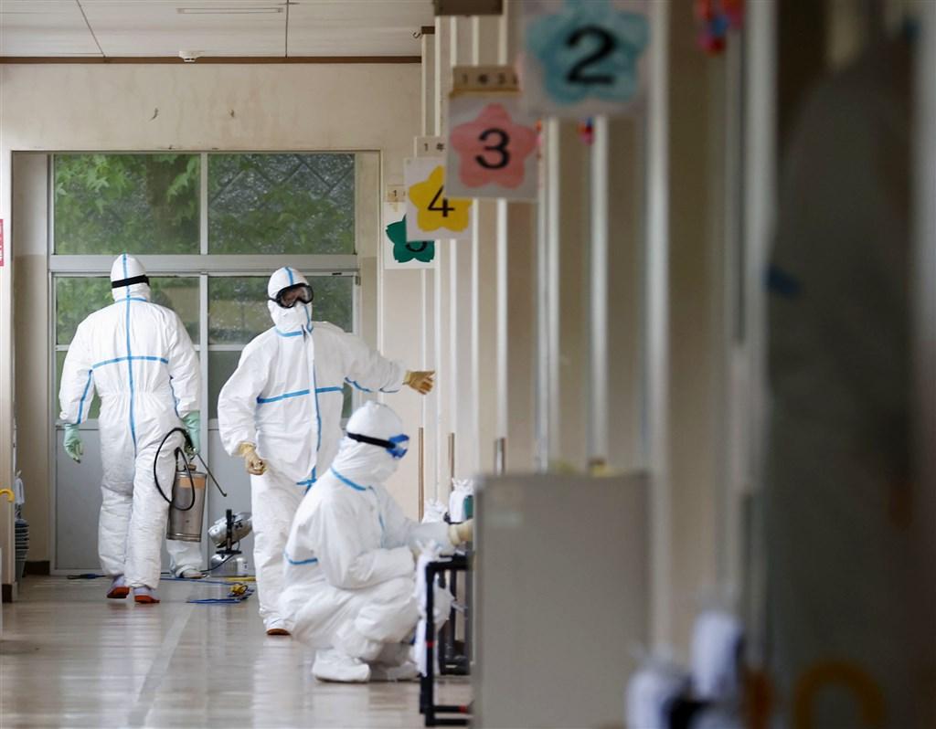 日本31日新添35起武漢肺炎確診病例,其中北九州市增12例,小學、醫院發生群聚感染。圖為防疫人員在爆發群聚感染的守恒國小消毒。(共同社提供)