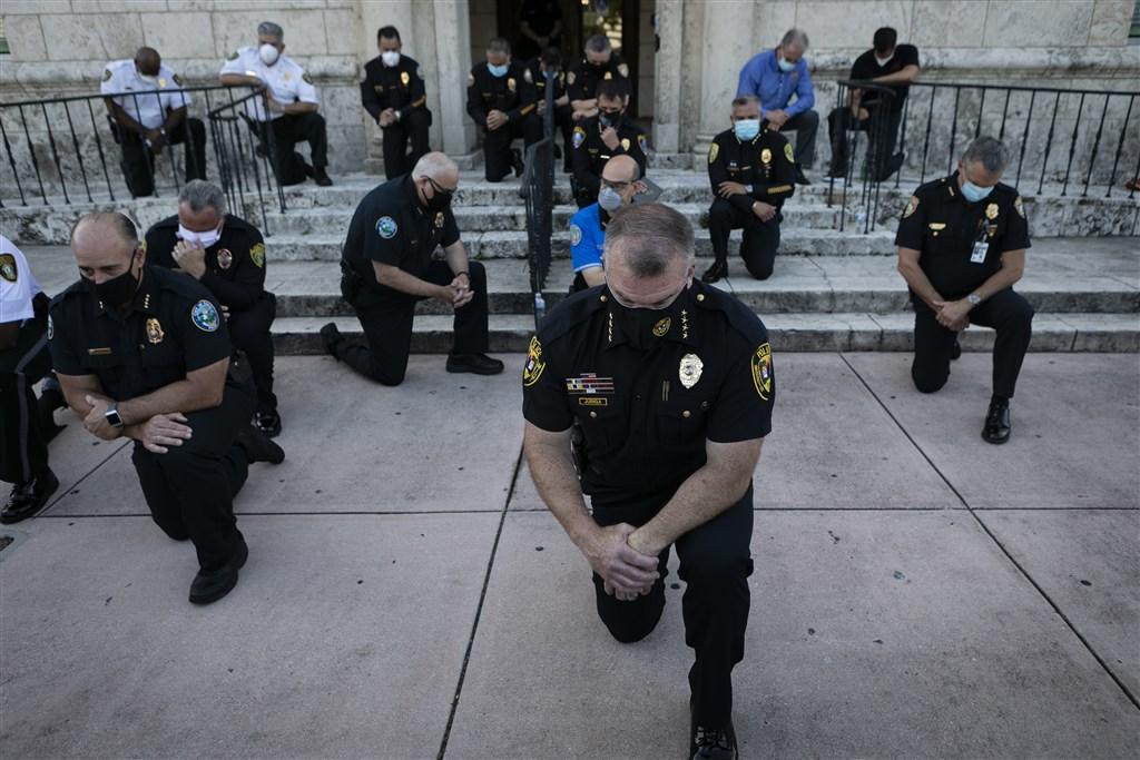 非裔美國男子佛洛伊德日前遭白人警察壓著脖子致死,在全美引發暴力示威。但佛州珊瑚牆市的抗議場面大不相同,來自不同警局的員警單膝跪地,與抗議群眾一同祈禱。(法新社提供)