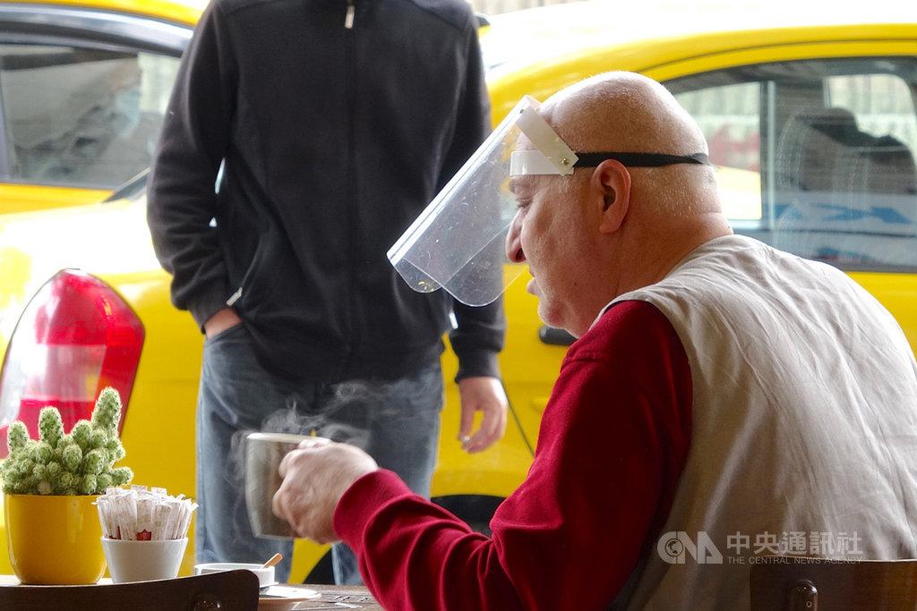 土耳其1日解除多項武漢肺炎防疫禁令,包括准許餐飲業恢復營業。一位民眾戴著面罩坐在首都安卡拉的一家餐館喝咖啡。中央社記者何宏儒安卡拉攝 109年6月2日
