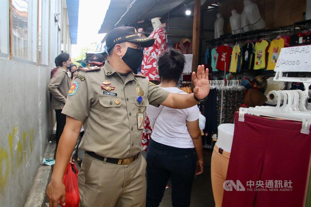 印尼防疫措施僅允許11種民生必需行業繼續運作,但實際上很多行業仍未停業。雅加達警方23日在開齋節前夕加強取締,但警方離開後,店家仍繼續營業。中央社記者石秀娟雅加達攝 109年5月25日