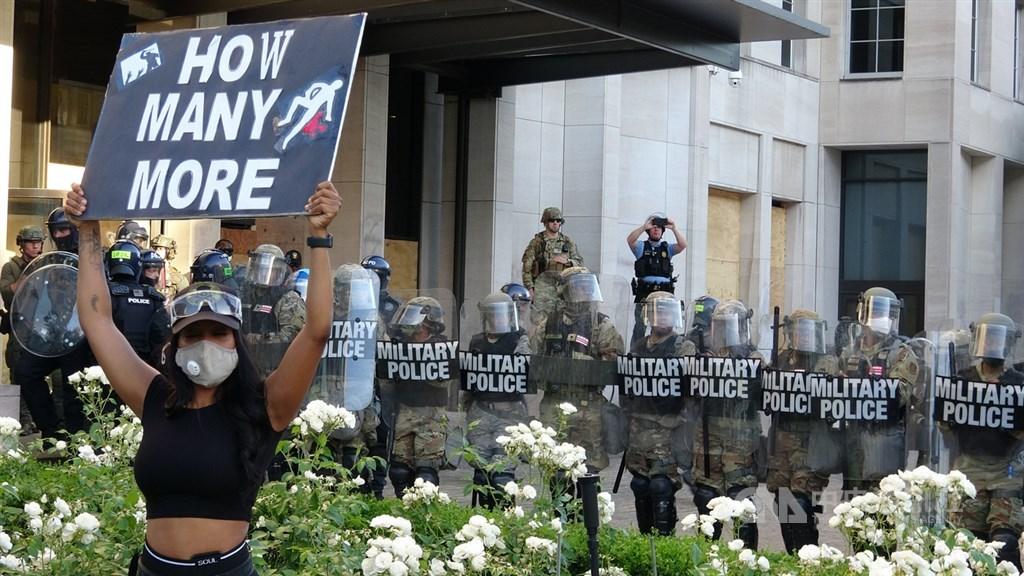 全美爆發反種族歧視抗議,上千民眾前往白宮前抗議。圖為一名年輕女子高舉標語站在軍警前抗議。中央社記者江今葉華盛頓攝 109年6月2日