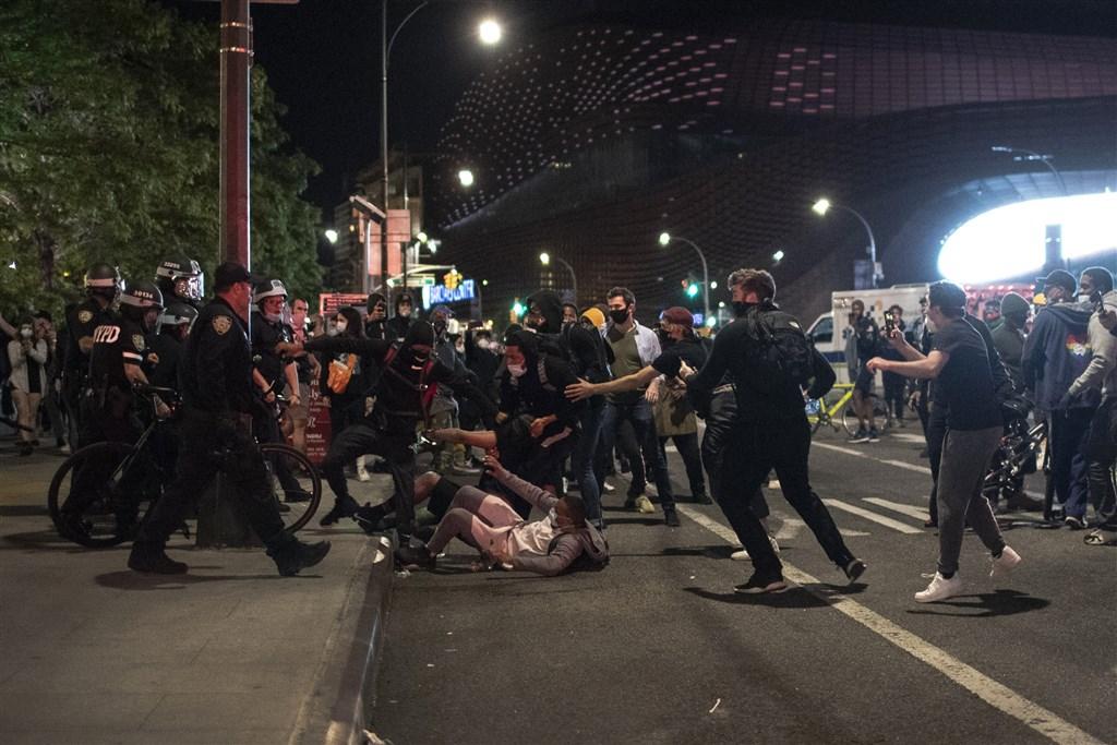 美國非裔男子佛洛伊德遭白人警察以膝壓頸喪命,各地掀起示威潮。紐約市1日晚間11時至2日清晨5時實施宵禁。圖為紐約布魯克林區示威民眾與警察發生衝突。(美聯社)