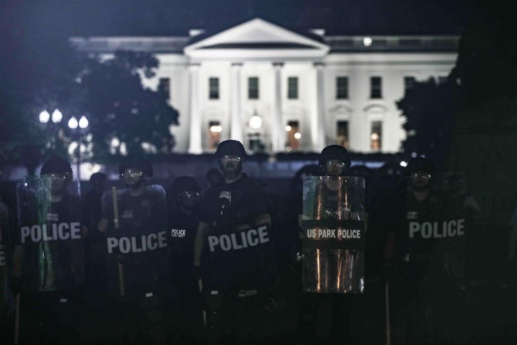 美國非裔男子佛洛伊德遭警方壓頸致死引發各地連日抗議,甚至出現暴力情事,總統川普1日譴責這是「國內恐怖行徑」。圖為持盾警員駐守白宮外。(安納杜魯新聞社提供)