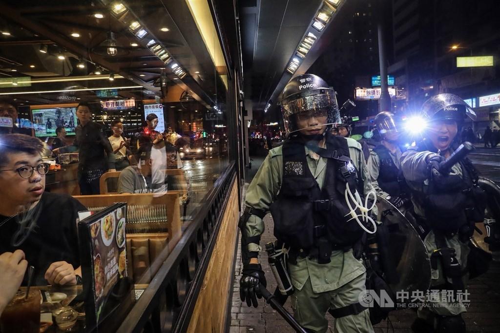 香港法庭17日裁定一名包圍警察總部、襲擊便衣員警的男子暴動罪和普通襲擊罪,這也是「反送中」後首宗經法庭審訊定罪的暴動罪案件。圖為2019年8月香港人被迫看著警察驅離示威者。(中央社檔案照片)