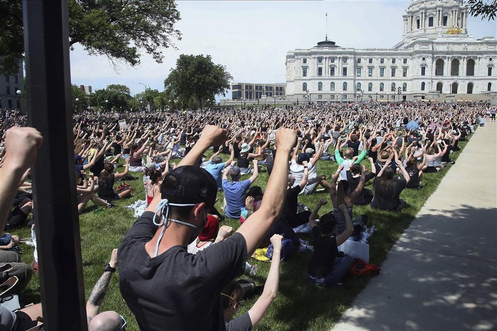數千人2日聚集在明尼蘇達州聖保羅的州議會大廈外靜坐,高舉雙手,對佛洛伊德之死表達哀悼。(美聯社)
