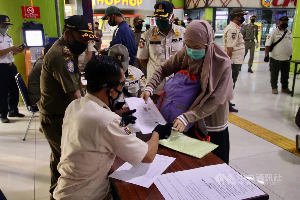 印尼在武漢肺炎疫區實施的人流限制措施5月中放寬,持健康證明及工作需要證明等文件的民眾可進出各大城市。圖為雅加達甘比爾車站3日檢查抵達旅客的文件。中央社記者石秀娟雅加達攝 109年6月4日