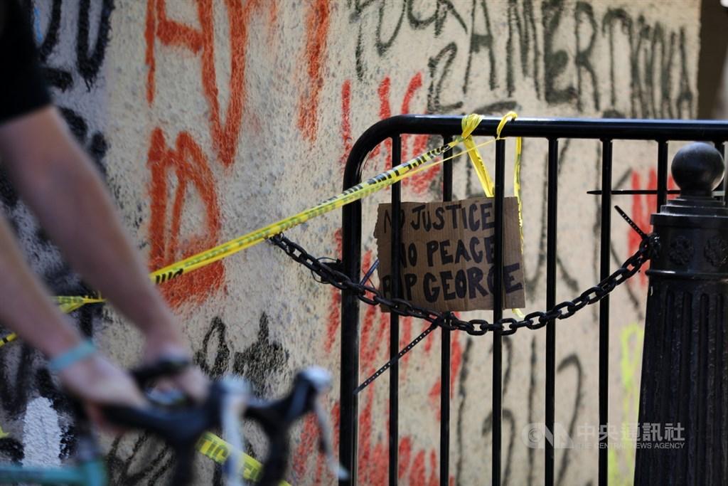 今年美國經濟因防疫封鎖措施而衰退,分析師預期,整體復甦還要很長時間,且還有示威潮等不確定因素待觀察。圖為白宮外建築物牆面佈滿塗鴉,柵欄上也掛著「沒有正義,沒有和平,佛洛伊德請安息」的紙板。中央社記者徐薇婷華盛頓攝 109年6月2日