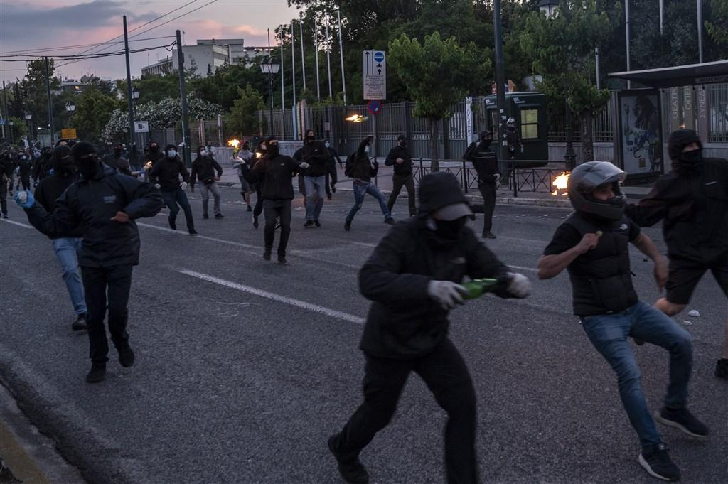 不滿種族主義與警方暴力的抗議群眾3日在雅典集會,朝希臘鎮暴警察丟擲汽油彈,警方則施放催淚瓦斯驅散人群。(法新社提供)